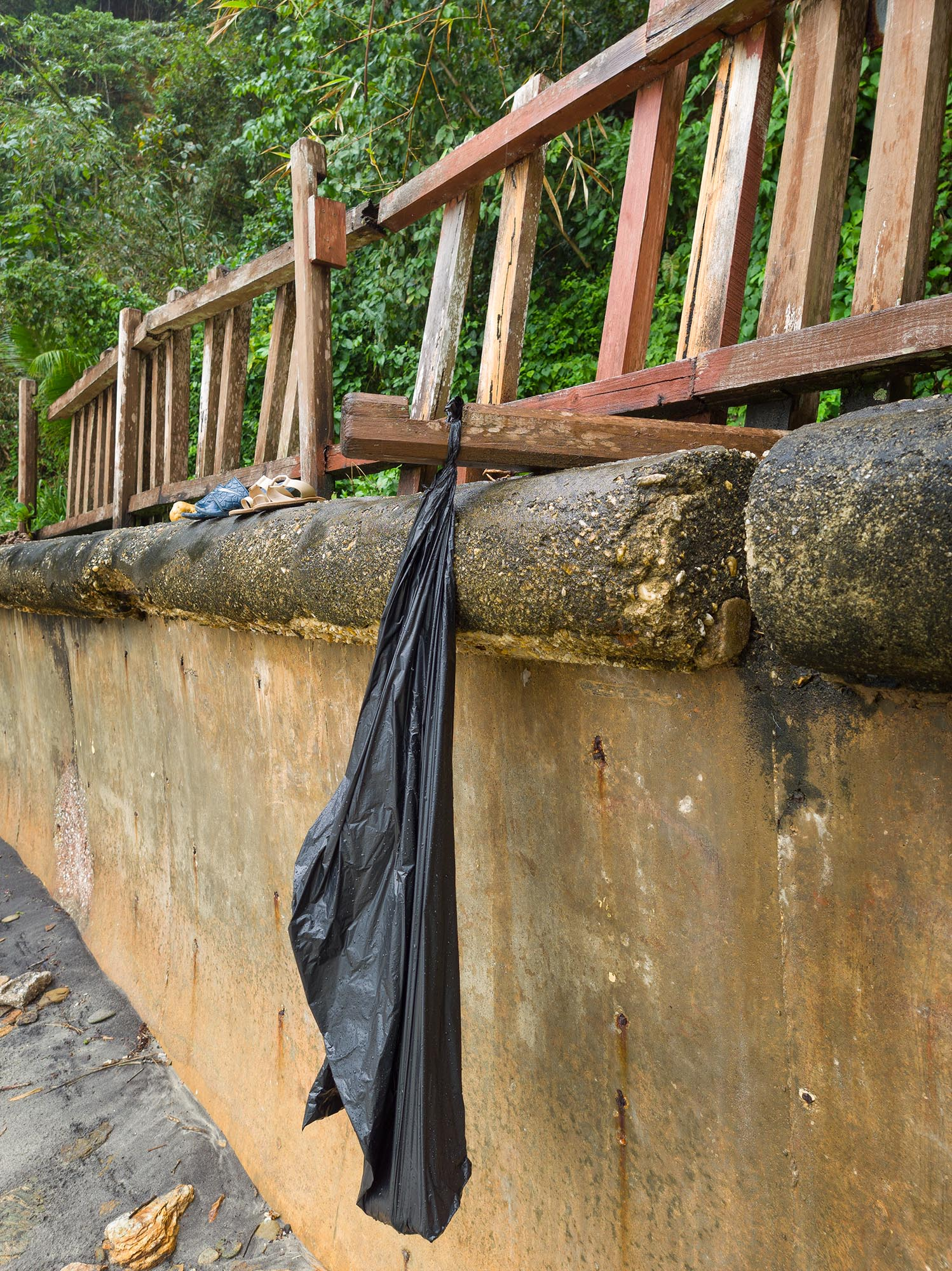 The collapse of the safety features of the beach are now institutionalised, as workers responsible for placing garbage bags for visitor use now hang them from bits of collapsed railing. Photo by Mark Lyndersay.