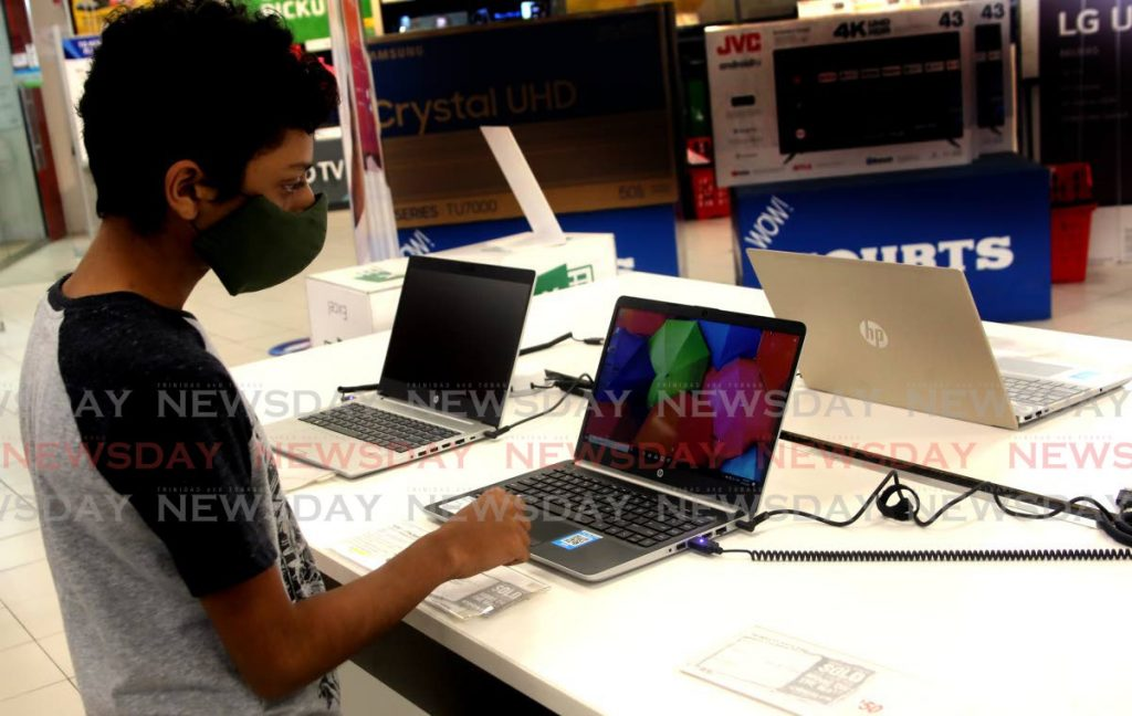 Matthew St Clair checks out laptops on sale at Courts Megastore in El Socorro. Young people are encouraged to find ways to destress from a higher than usual use of digital devices. - Photo by Sureash Cholai