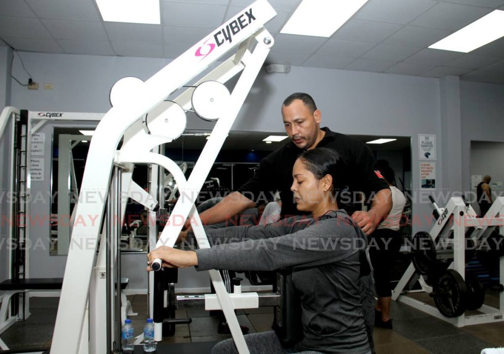 In this December 9, 2020 file photo, trainer Edimer Ortiz assists Nefertiti Loubon while she uses a seated row machine at the Millenium Gym, Tunapuna. - AYANNA KINSALE