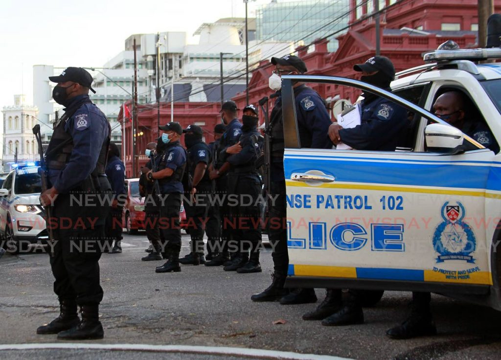 FILE PHOTO: Police, all wearing masks, stand ready to do their duty outside the Red House, Port of Spain, in February. Police Commissioner Gary Griffith says officers will step up their efforts in policing covid19 regulations. - ROGER JACOB