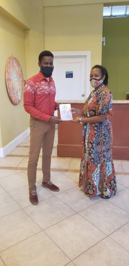 Amos Paul is presented with a copy of the book by first-time author Kiona Assing during a launch on Friday last at the Magdalena Grand Beach and Golf Resort.  - Kinnesha George-Harry