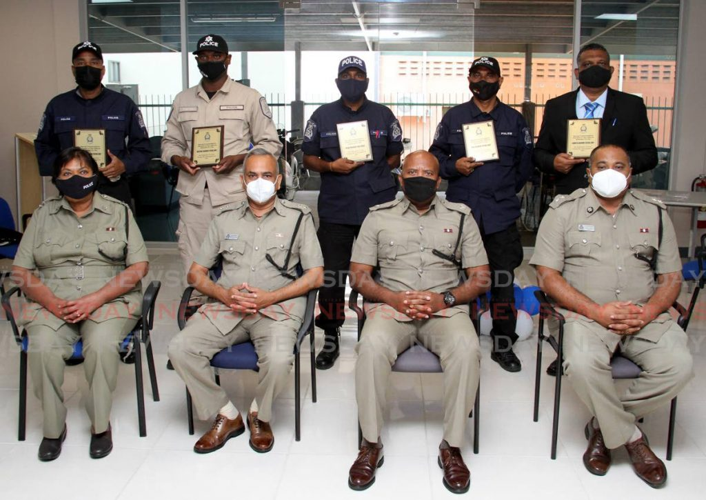 Inspector Orcil Phillip, Inspector Damian Cadet, Inspector Sunil Harrylal, Inspector Danny Ragbir and Inspector Harold Ouguiste (back row from left) hold commendation awards during a ceremony at the Traffic and Highway Patrol Unit, El Socorro on Thursday. In front row ASP Nazmoon Khan-Mohammed, Supt Ramjan Rampersad, Snr Supt Wayne Mystar and ASP David Guelmo.  - Photo by Angelo Marcelle