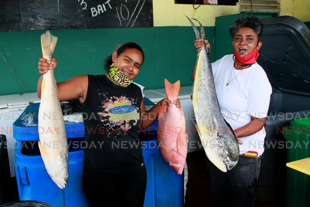Mariella Alleng and her mother Juliet Joseph, both fisherwomen, concentrate on their fish retail business at the St James Fishing Depot after their boat engine was stolen. - PHOTO BY ROGER JACOB