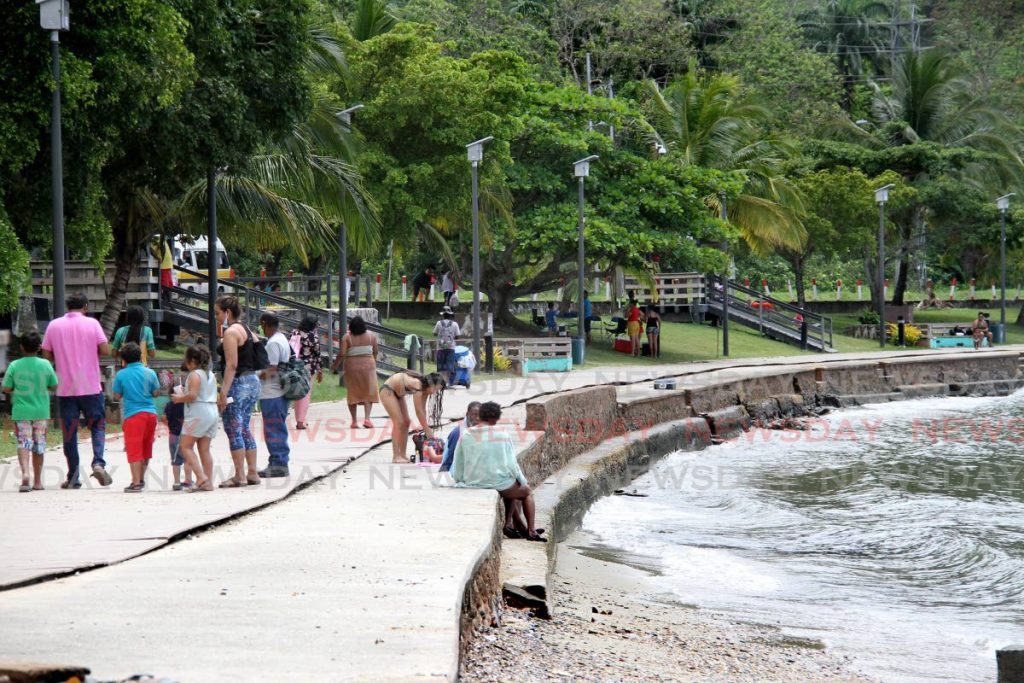 People stroll along the Chaguaramas boardwalk, some taking a dip in the bay, on Good Friday.  - Photo by Angelo Marcelle