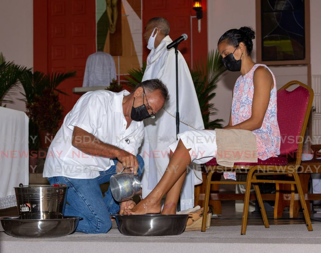 Fr Leslie Tang Kai stands aside as Andrew Llanos washes the feet of his wife Dana at Scarborough RC Church on Holy Thursday. In his sermon on Good Friday the priest called on the PNM and PDP to work together to solve the THA six-six deadlock. - Photo by David Reid