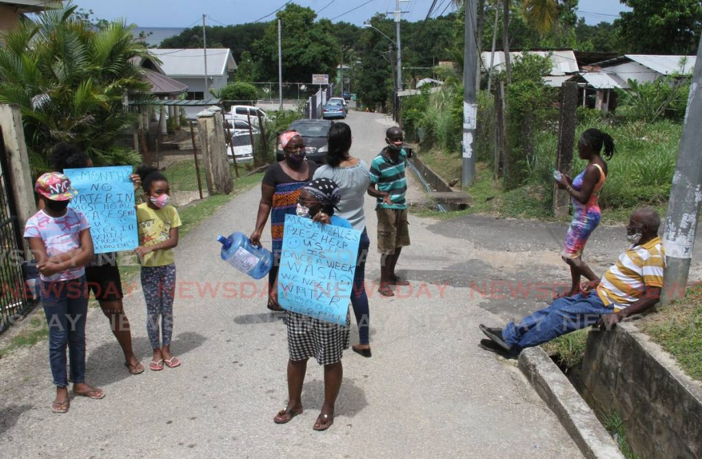 Residents of Rosehill Street, Claxton Bay on Saturday appeal for pipe-bourne water which they say they have not had for months.  - Photo by Angelo Marcelle