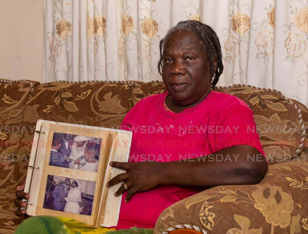 MISSING 'GREGGY': Sherma Greig displays her wedding album during an interview at her Moriah home, on her husband Bernard Greig who was Tobago's first covid19 fatality. PHOTO BY DAVID REID -
