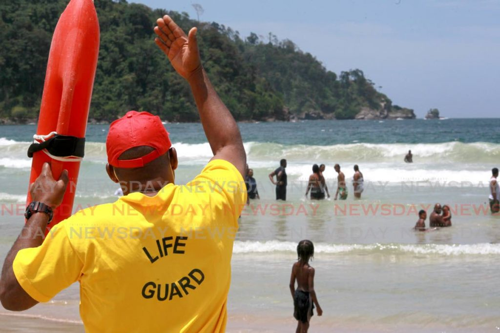 A lifeguard signals swimmers to come closer to shore at Maracas Bay over the Easter weekend. - Photo by Roger Jacob