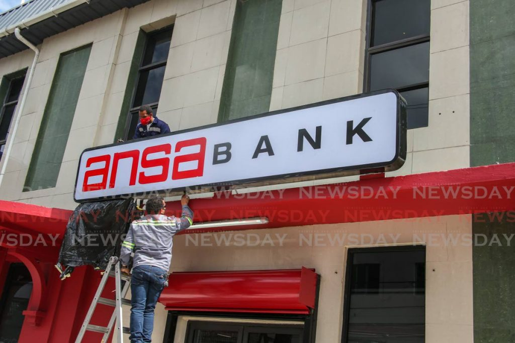 REBRANDED: Workmen install new sinage for Ansa Bank which recently bought out Bank of Baroda. The rebranding exercise began in San Fernando on Monday and will continue in Port of Spain and Chaguanas this week. Photo by Jeff K. Mayers