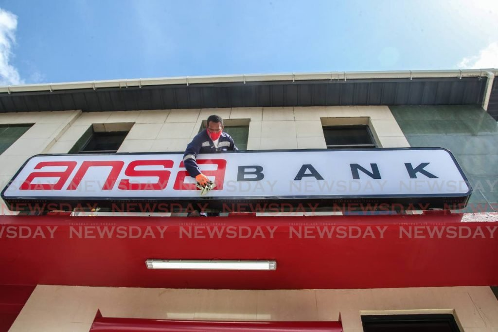 A worker puts finishing touches on the Ansa Bank sign at the St James Street, San Fernando branch on Monday. Ansa Bank officially opened in Port of Spain, San Fernando and Chaguanas on Tuesday. - Photo by Jeff Mayers