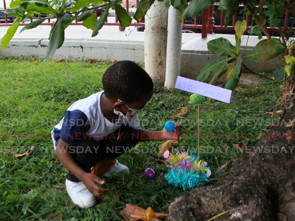 Kaiis Charles finds Easter eggs hidden at the base of a tree at Woodford Square as part of the Port of Spain City Corporation's Easter Egg Treasure Hunt on Monday.  Photo by Roger Jacob