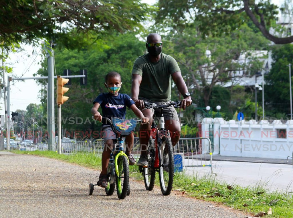 Father and Son, little Jasiel Figaro cycles with his father Micky Figaro around the Queen's Park Savannah on Sunday. Photo by Roger Jacob