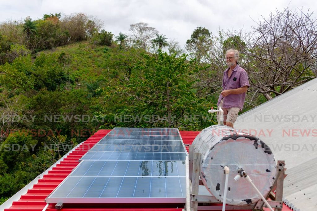 Wildlife conservator Ian Wright looks out at the forest view over the solar panels that powers his home in Mason Hall, Tobago. Photo by David Reid.