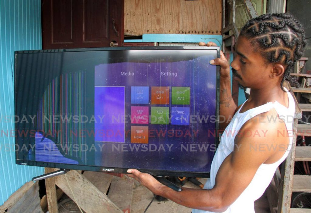 Silk Cotton Drive, Marabella resident Lennard Redhead, shows his damaged television which he claims fell because of the NiQuan Energy Plantś explosion on Wednesday. - Photo by Angelo Marcelle