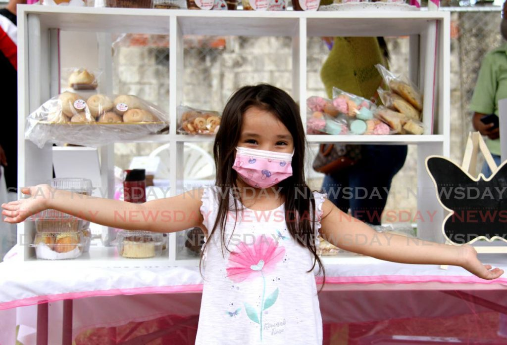 Five year old Victoria Baquero stands in front the cart of Delicious Sweet at the launch of Flavourama Festival on Barbados Road, St. Clair. - Photo by Ayanna Kinsale