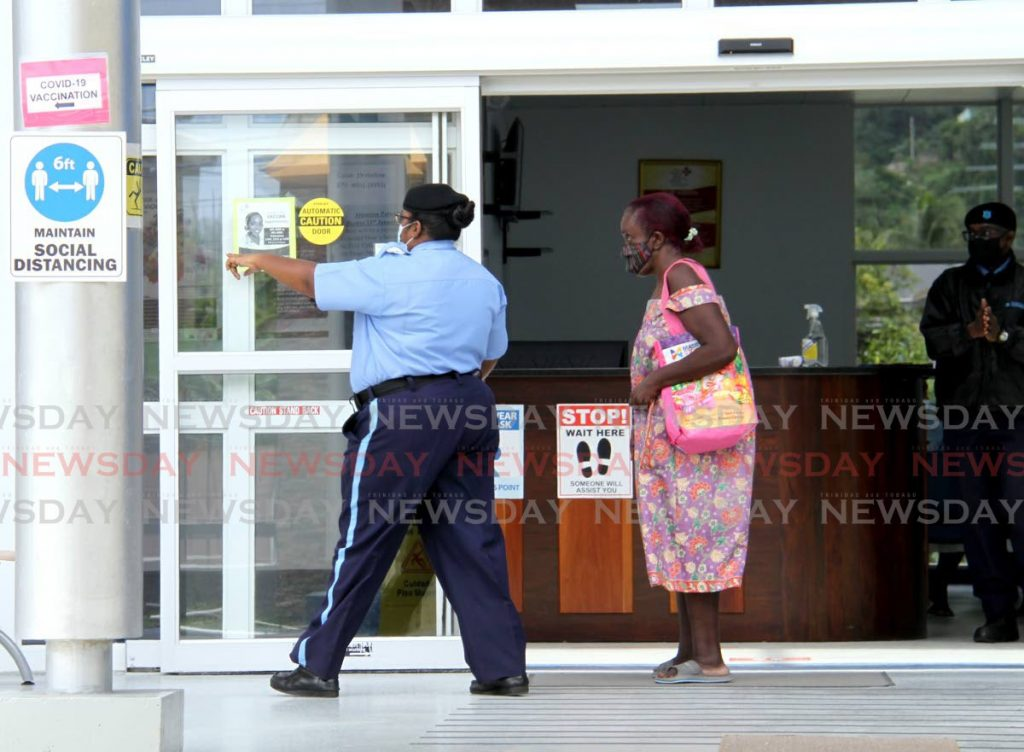 In this file photo, a security guard directs a visitor to the waiting tent at the Diego Martin Health Centre on Wendy Fitzwilliam Boulevard, Diego Martin. - AYANNA KINSALE