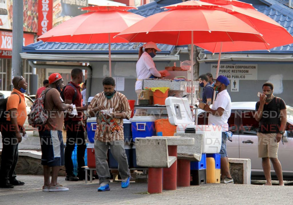 FILE PHOTO: Customers buy and eat doubles at a popular vendor's stand on the Brian Lara Promenade, Port of Spain, last Wednesday. At one point during 'lockdowns' last year, intinerant vending was banned altogether. Further increases in covid19 spread can force government to consider such measures again. - AYANNA KINSALE
