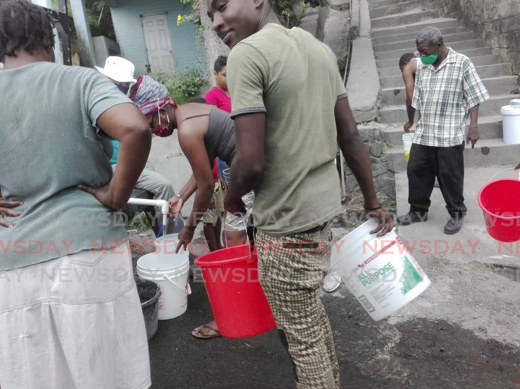 BUCKETS IN HAND: Vincentians in Edinboro wait with buckets in hand to get water from a truck as the country grabbles with dwindling water supplies due to contamination of the water courses and water treatment plants by ash-fall caused by the eruption of the La Soufriere volcano. PHOTO BY STEPHON NICHOLAS - Stephon Nicholas
