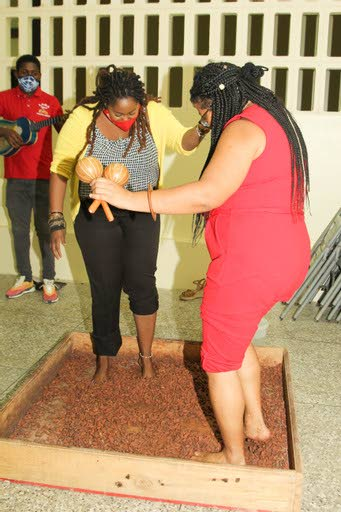 "Digicel Foundation Operations Manager, Cindy Ann Currency joins in the fun and learns the art of ""Dancing De Cocoa"" with Founder of the Lopinot Tourism Association Donna Mora. -"