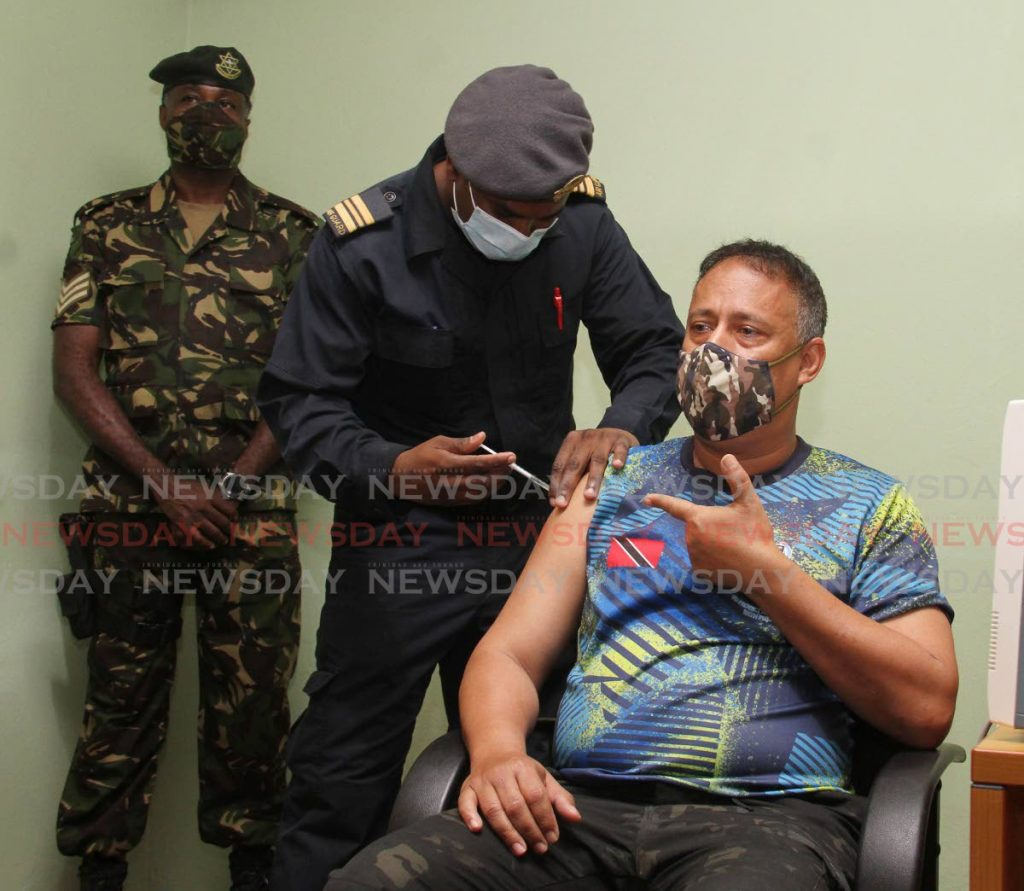 Police Commissioner Gary Griffith receives the covid19 vaccine from squadron leader/registered nurse Marvin Bocas at Camp Ogden, St James on Saturday. - Photo by Angelo Marcelle