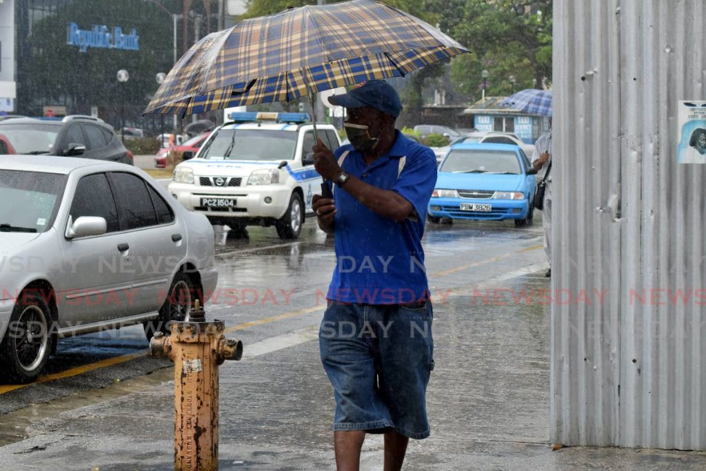 File photo: A man holds his umbrella with a firm grip as the wind and rain blew on him while he was trying to cross at the corner of Henry street and Independence Square, Port of Spain. Photo by Vidya Thurab