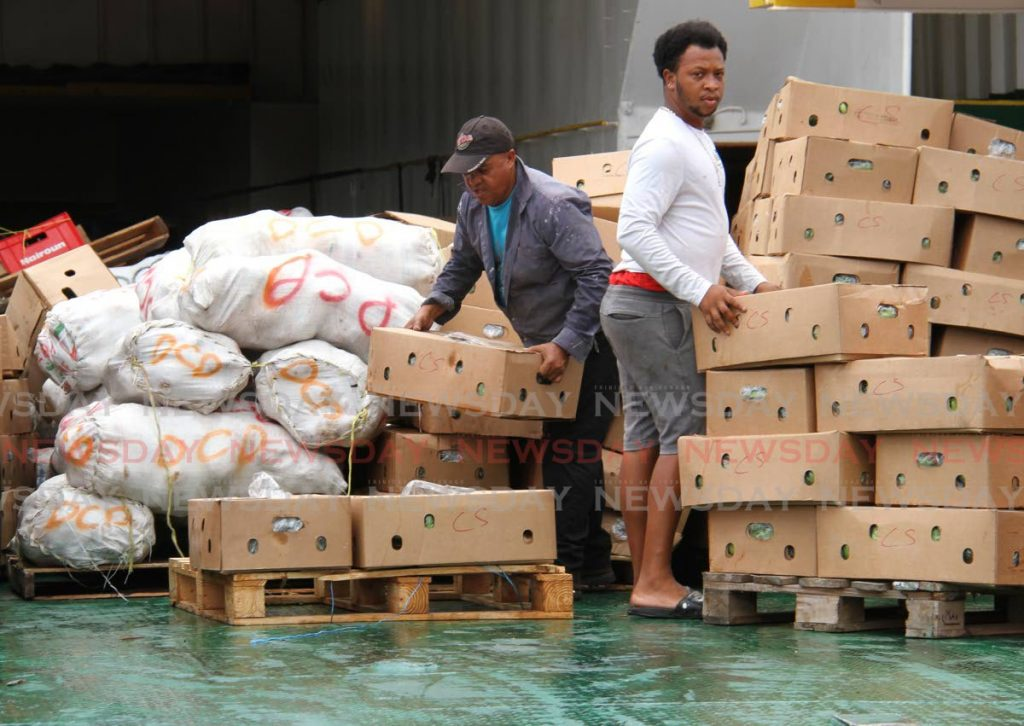 Workers unpack produce from the Admiral Bay 1 after it brought in goods from St. Vincent and the Grenadines to Trinidad at the Port Authority. - Phoyo by Ayanna Kinsale