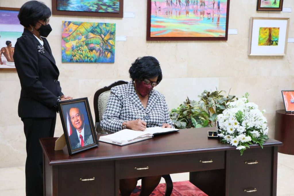 PRESIDENT Paula-Mae Weekes (right) signs a condolence book for former senator, the late Franklin Khan, at the Red House on Wednesday, watched by Senate President Christine Kangaloo.   -