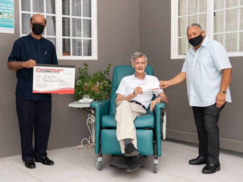 Chairman of the Past Cricketers Society Justice Prakash Moosai, left, and executive member Gary Almandoz, right, present a cheque to former TT and West Indies cricketer Charlie Davis. PHOTO COURTESY CURTIS KHAN  -