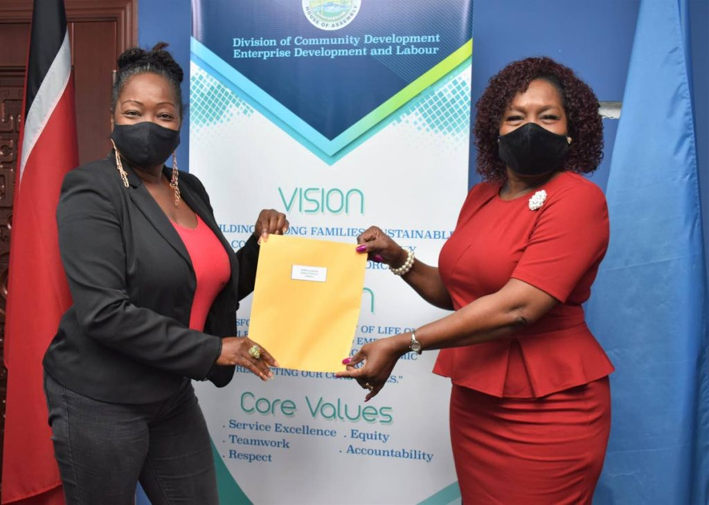Secretary of Community Development, Enterprise Development and Labour Marslyn Melville-Jack, right, distributes a covid19 relief grant to a business owner on Tuesday at the Business Development Unit, Scarborough. - THA