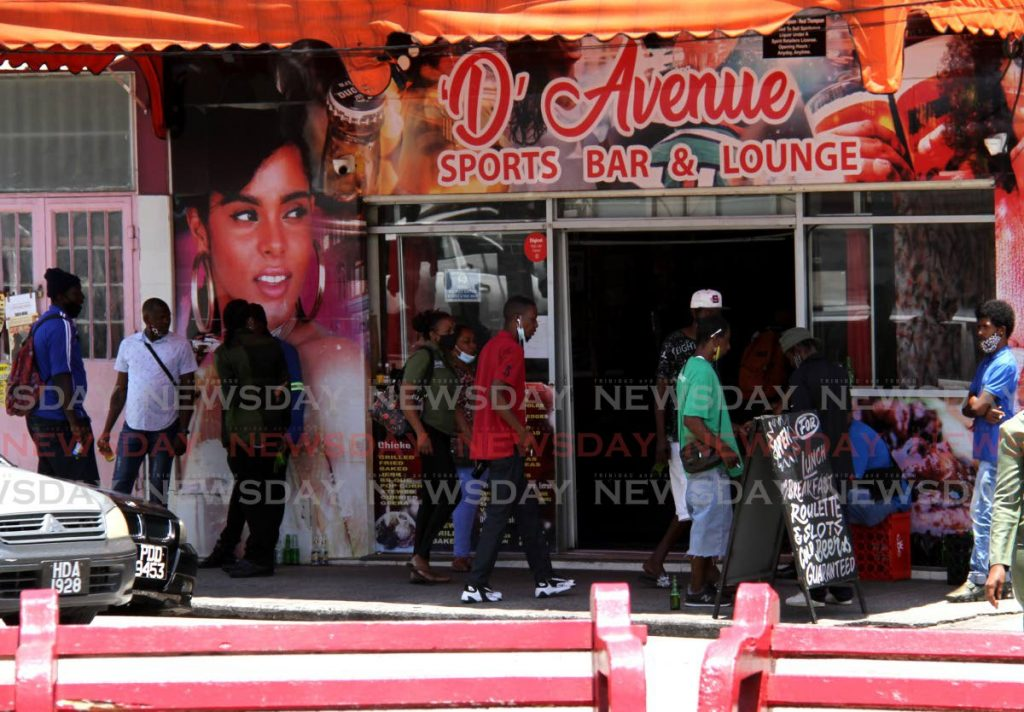 Some patrons gather outside a bar along Independence Square, Port of Spain in April. - AYANNA KINSALE