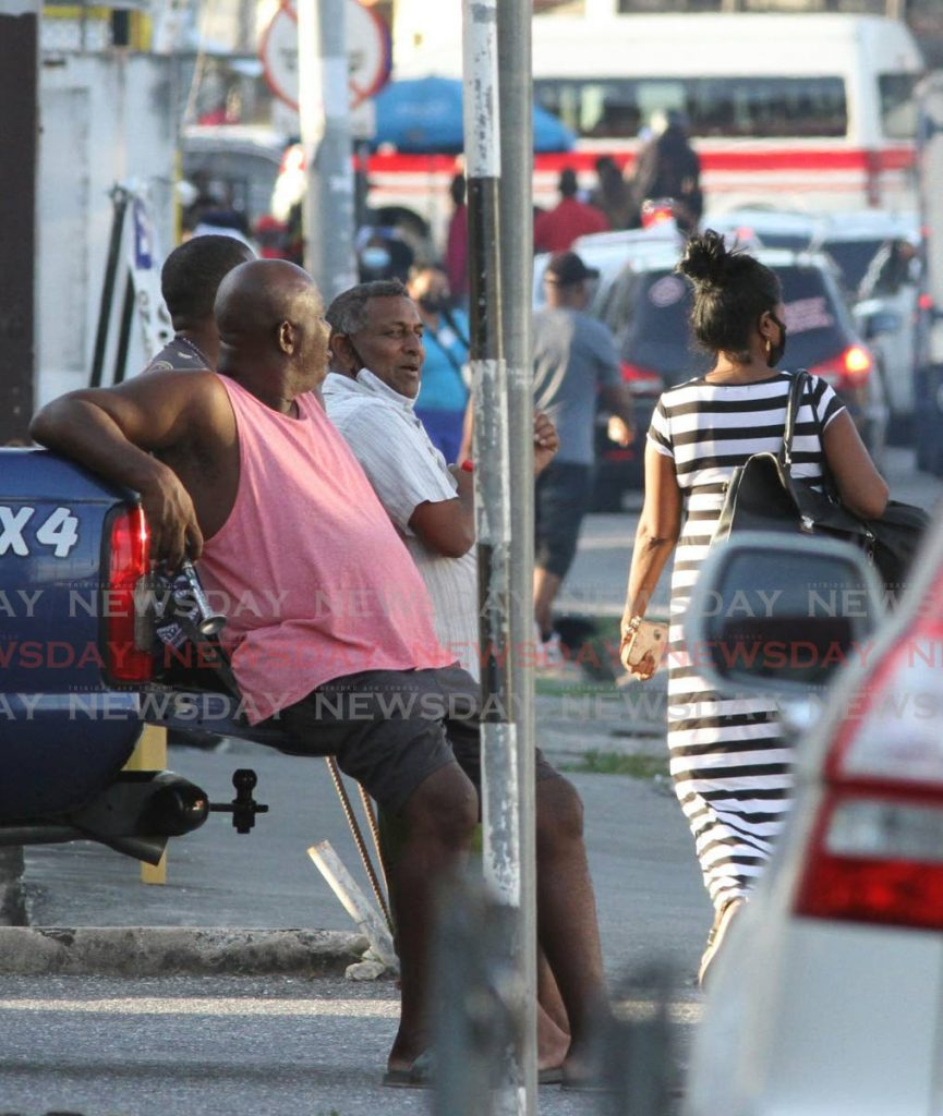 Despite public health guidelines, these men sit in the cab of a van chat without face mask along the Southern Main Road, Curepe on Thursday. -Photo by Angelo Marcelle