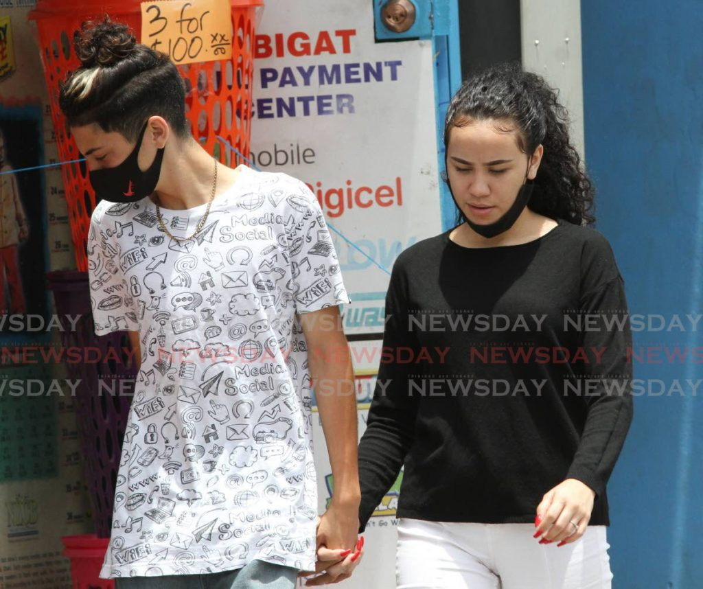 RIGHT AND WRONG: This couple provided contrast in the right and wrong ways to wear your face mask as they strolled hand in hand along the street in Chaguanas. Photo by Angelo Marcelle