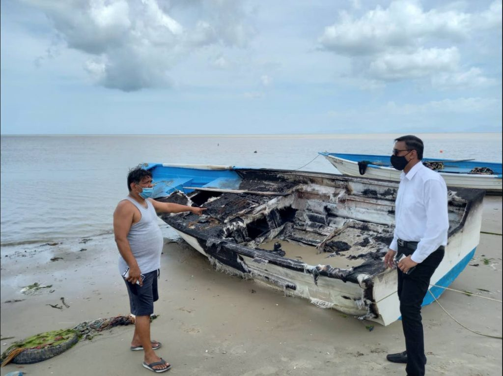 In this file photo, President of Calibay Fishing Association, Imtiaz Khan, shows Couva North MP Ravi Ratiram a boat which was vandalised by pirates - Photo by Marvin Hamilton