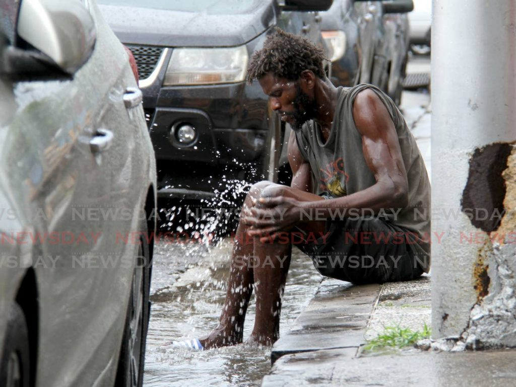 This man uses the rain water flowing from the drain to wash his skin on Henry Street, Port of Spain. - Photo by Ayanna Kinsale