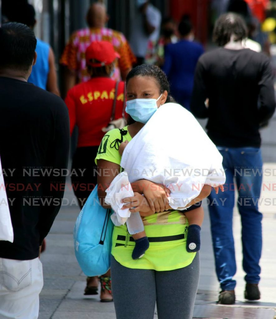 In this August 2020 photo, a woman wearing a face mask walks down Frederick St, Port of Spain, with a baby in her arms. According to psychologist and UWI lecturer Dr Katija Khan, mothers and, by extension, women in the homes have been quietly bearing the brunt of the pandemic's societal consequences. Photo by Sureash Cholai