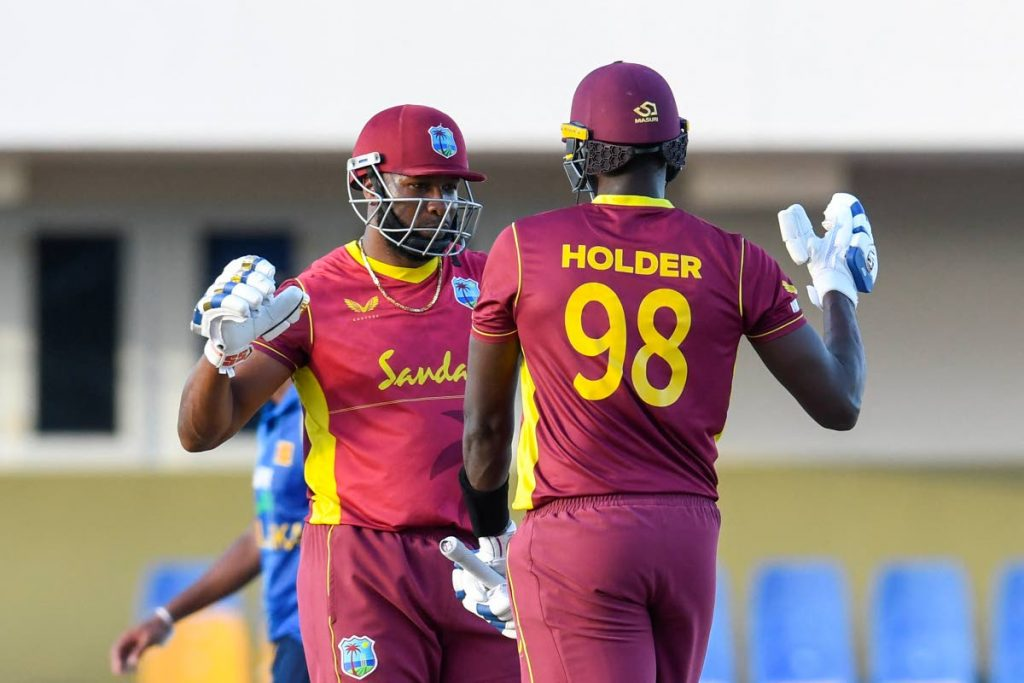 In this March 14, 2021 file photo, Kieron Pollard (left) and Jason Holder of West Indies celebrate winning the 3rd and final ODI match between West Indies and Sri Lanka at Vivian Richards Cricket Stadium in North Sound, Antigua.  - (AFP PHOTO)