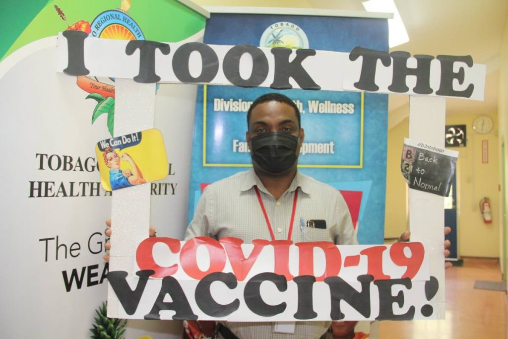 Kern Cowan displays a sign showing confidence in the covid19 vaccine after taking his jab in Tobago.  PHOTO COURTESY DIVISION OF HEALTH -