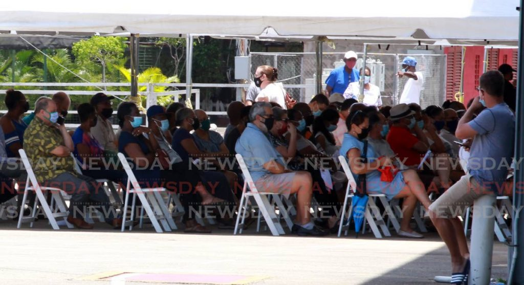 Scores of people wait to be vaccinated at Queen's Park Savannah, Port of Spain on April 25. Government resumes the vaccination programme on Monday. - PHOTO BY ROGER JACOB