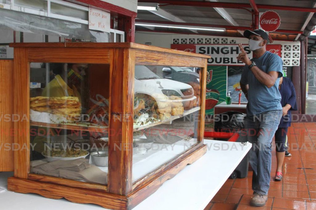 A customer places an order at Singh's Doubles in Debe. - Photo by Marvin Hamilton