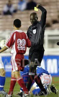 Former TT referee Noel Bynoe, right, gives a player a yellow card during his officiating days. - courtesy TT Football Association