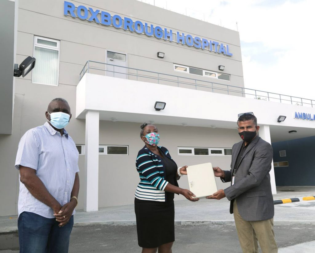 Udecott construction manager Brent Siboo, right, in recent handover of the keys to the Roxborough hospital to Cherryl-Ann Solomon-Mitchell, Administrator, Division of Health, Wellness and Family Development. Also present was Westly Orr, interim CEO, TRHA. - THA