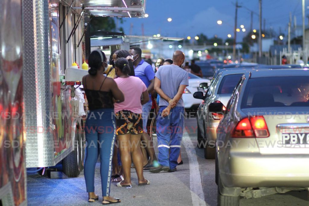 Customers and cars line up near food vendors at Cross Crossing, San Fernando on Monday evening. - Marvin Hamilton