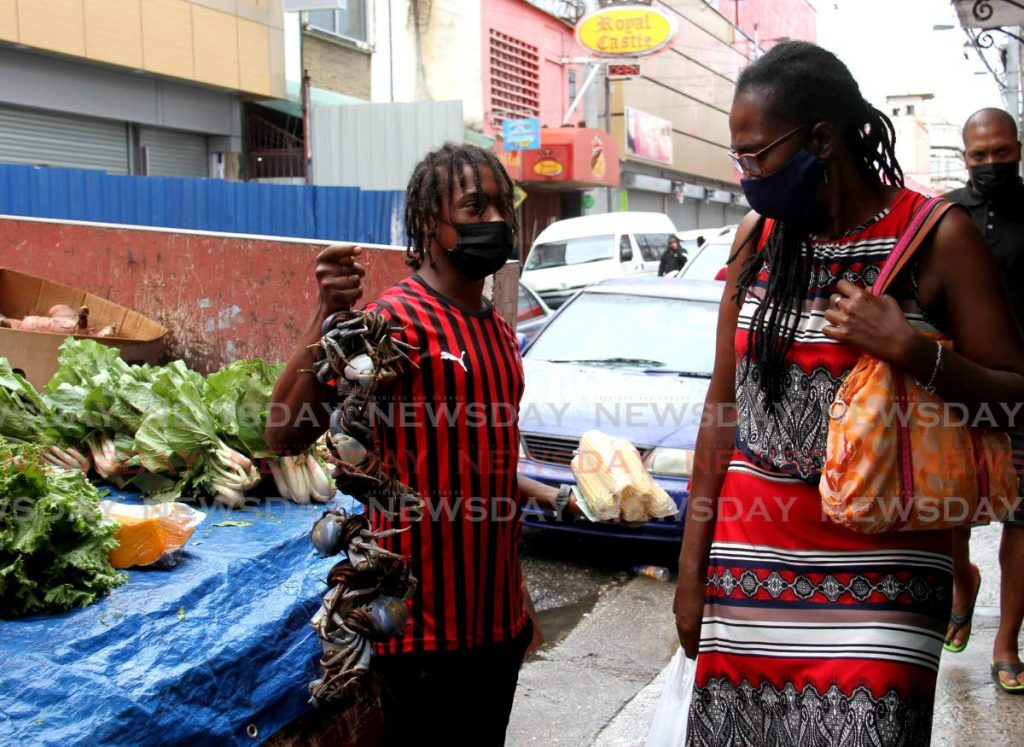 Vendor Joeninho Romel Melville tries to sell crabs to a pedestrian on Charlotte Street, Port of Spain, Tuesday. - AYANNA KINSALE