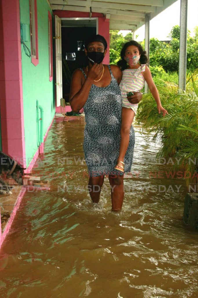 Lystra Maloney holds her granddaughter Jessica as she stands in the entrance to her flooded home, Cunapo Southern Main Road, Coalmine, Sangre Grande, Tuesday.  Photo by Roger Jacob