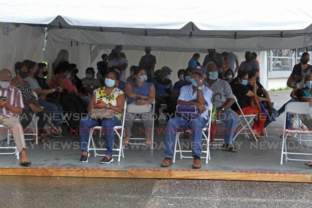 In this May 5 file photo, people wait for their names to be called outside the Southern Academy for the Performing Arts on in San Fernando. Photo by Marvin Hamilton