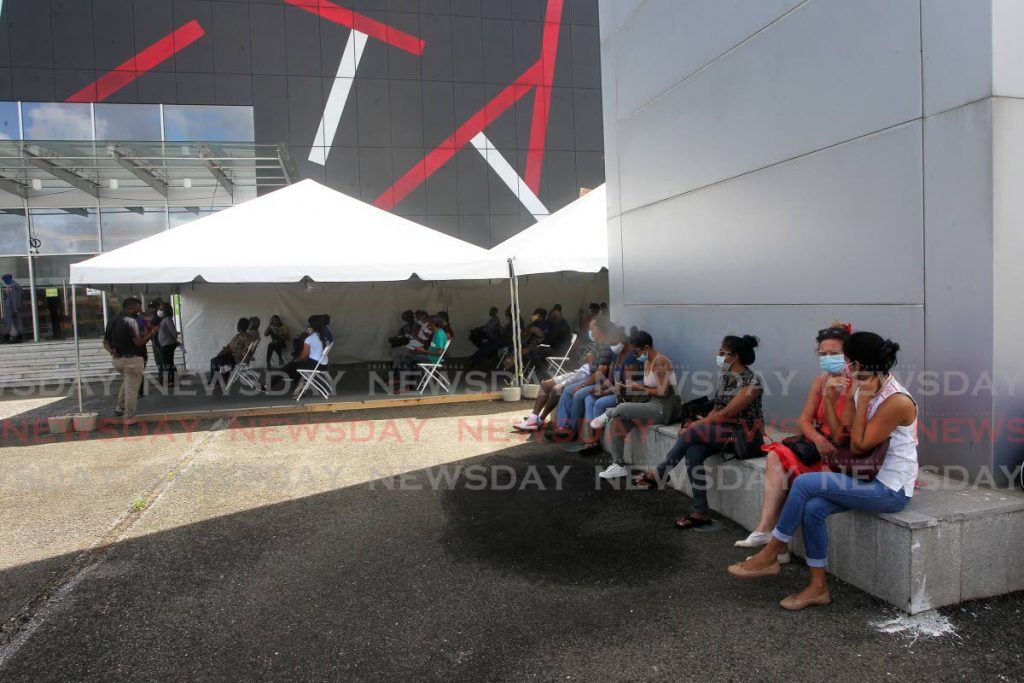 In this May 6 file photo, people await covid19 vaccines at SAPA, San Fernando. Photo by  Lincoln Holder