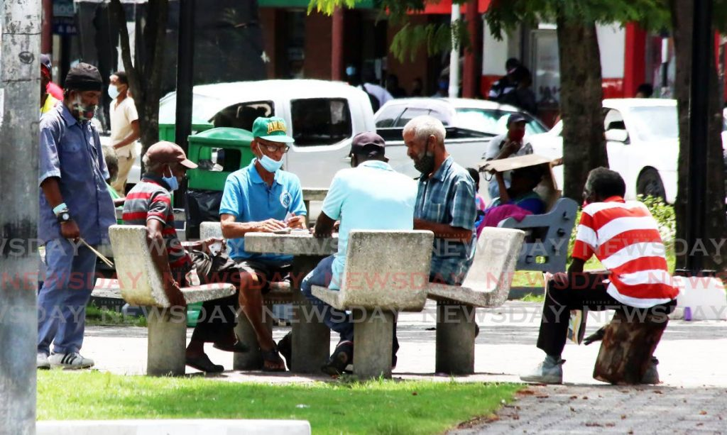 In this file photo these elderly men chose not to wear their masks properly as they hung out at the Brian Lara Promenade in Port of Spain on May 6. Photo by Sureash Cholai