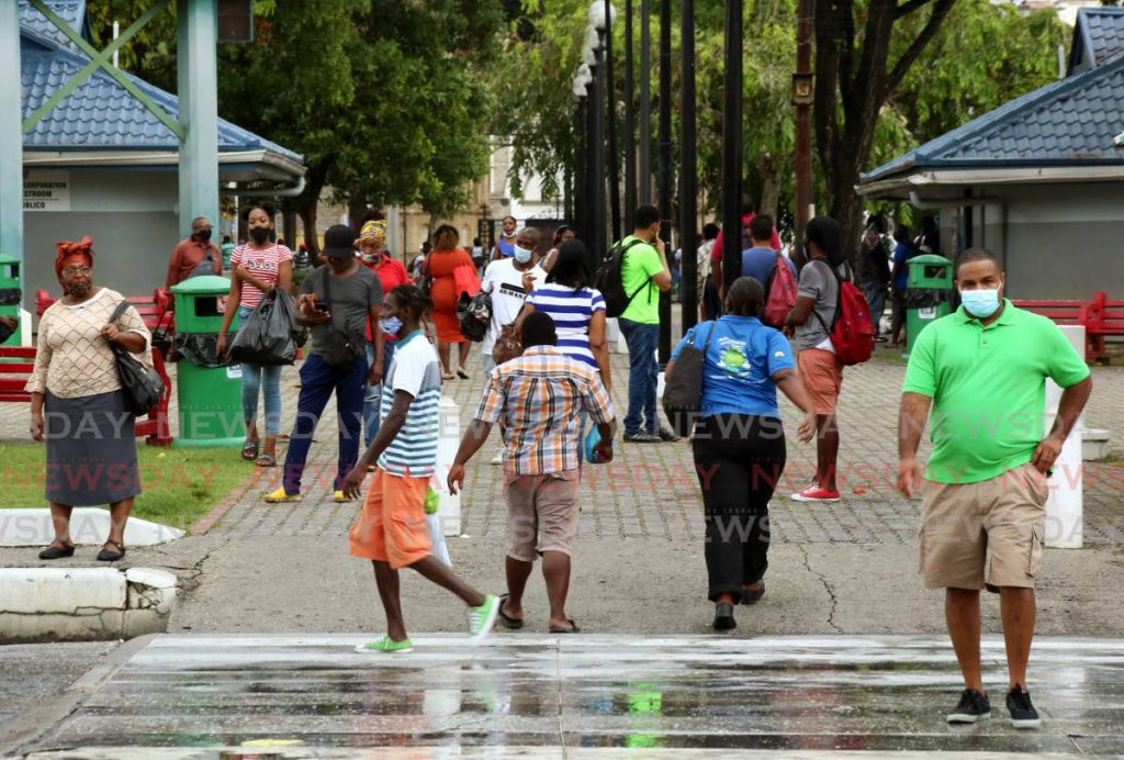 NARY A CARE: All caution and physical distancing are thrown out the window as these people go about their business along the Brian Lara Promenade in Port of Spain. PHOTO BY SUREASH CHOLAI   -
