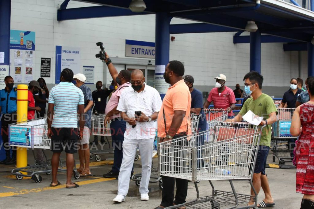 Pricesmart customers still hoping they would have reopen, wait with their trolleys outside the Port of Spain branch at Movietowne. Photo by Sureash Cholai