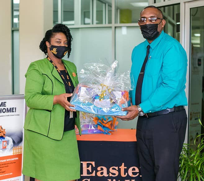 Antoinette Alexander, left, Craig Business Development Officer at Eastern Credit Union Co-operative Society Ltd presents Phillip Rochford, acting School's Supervisor II with tablets for primary schools. - THA